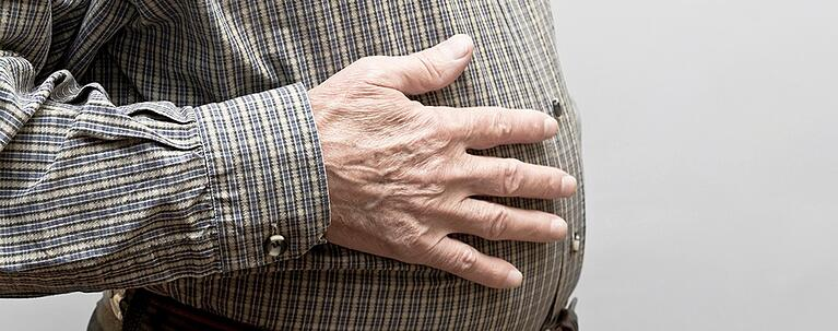 stomacch issues and aging a senior man with hand on stomach